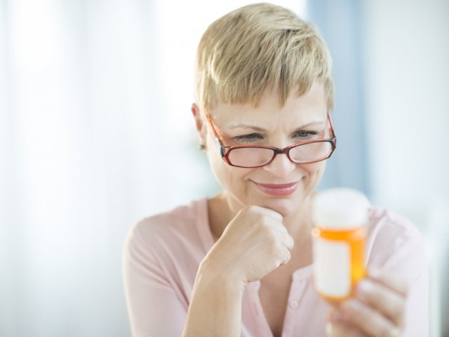 Woman Reading Label On Pill Bottle
