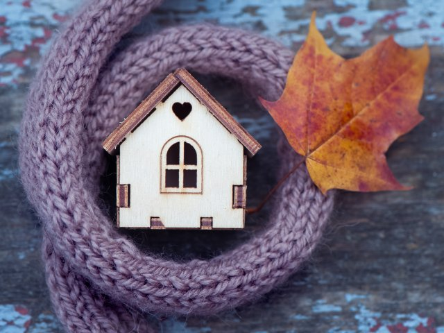 toy house is wrapped in a warm scarf with an autumn leaf.
