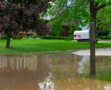 A suburban Midwestern neighborhood mailbox on a flooded street after a storm