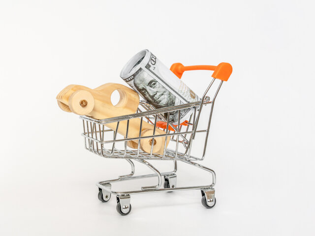 House model in mini shopping cart with stack of coins money on wooden table for residential investment