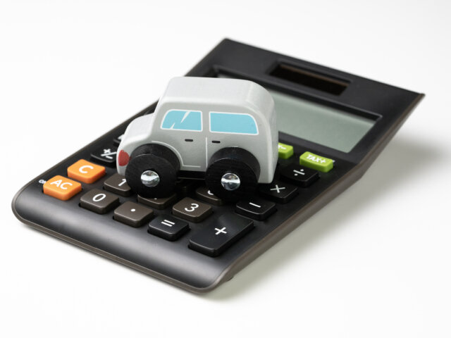 Car leasing, rental or insurance and maintenance calculation concept, cute wooden small toy car parking on black calculator on white background, down payment, installment for auto market