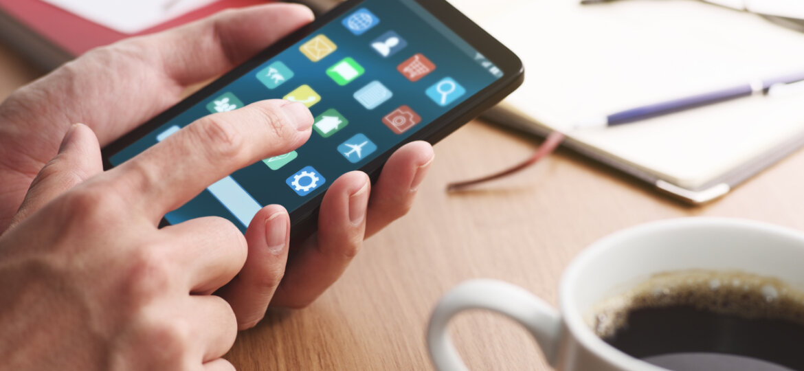 Closeup of male hands touching smartphone screen for using app at table.