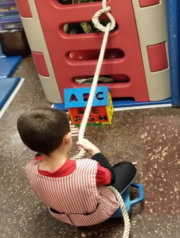 Picture of student sitting on scooter using a rope to pull himself towards an alphabet puzzle shaped like a house