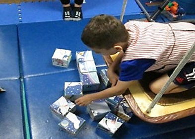 student on platform swing looking at cube shaped puzzle pieces