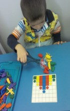 "Student completing a puzzle using a ""grabber"" to manipulate the materials"