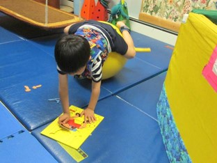 this photo shows a boy who is lying on his stomach over a physioball. His back and neck are extended while he engages the spatial orientation of puzzle pieces.