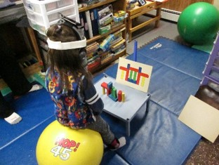 this photo shows a child who is sitting on a physioball while engaging spatial orientation of building a tower of blocks.  The back is extended while the head is straight upright.