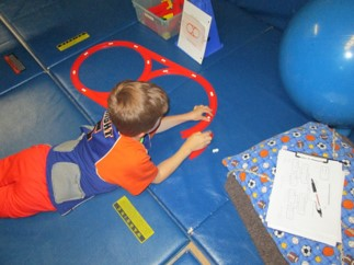 A boy is building a track with the layout in a figure 8
