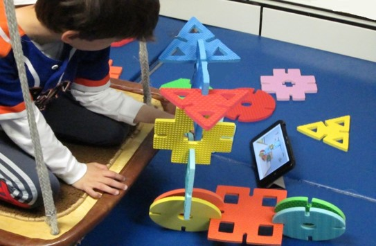 This photo shows a boy building a scooter from over sized geometric shapes while kneeling on a flat swing and following directions shown on an iPad