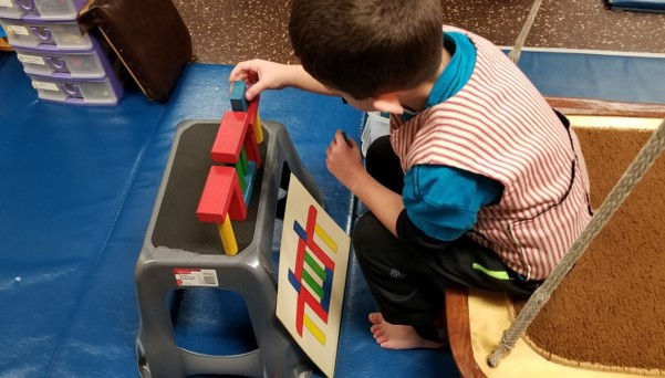 This image shows a boy sitting on a flat swing as he builds a tower of blocks