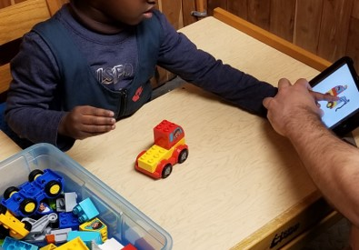 This photo shows a boy pointing to a Duplo car on a digital tablet