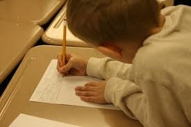 This is a photo of a boy holding a paper still with one hand while the other hand grasps a pencil for handwriting