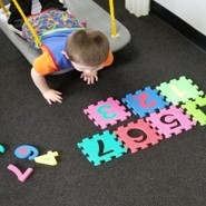 This photo shows a child selecting large foam numbers and placing them into corresponding floor tiles