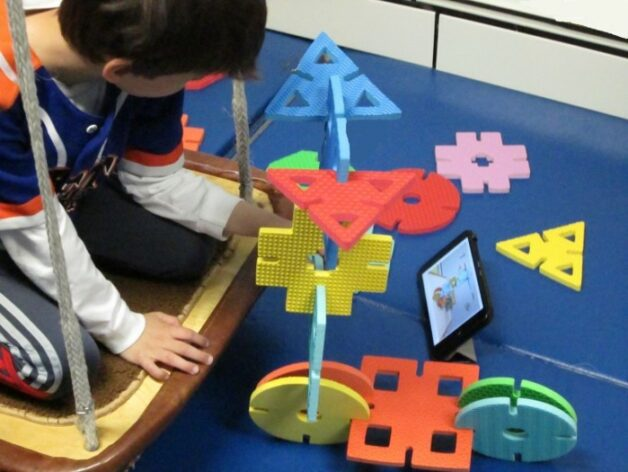 This is an image of a child who is using large foam shapes to build a toy scooter that matches the steps shown on a tablet