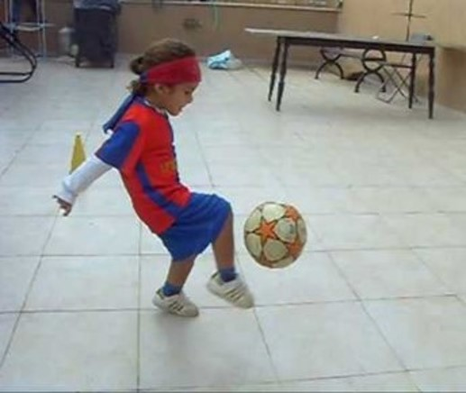 This is an  image of a youngster kicking a soccer ball.  The youngsters' head is  held in a vertical alignment while the arms and legs engage the soccer ball.
