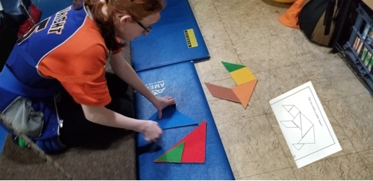 This image shows a girl at work on the floor .  She is using large felt tangram pieces to  construct a puzzle of a polar bear from an outline.