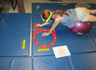 This image of a girl who is prone lying over a physioball is strengthening her back while copying track layouts from a diagram