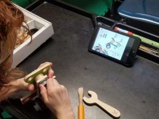 This is a photo of a boy who is using tools to build an airplane from a construction toy as shown on the tablet
