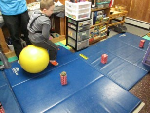 This photo shows a boy on a hop ball who is hopping around obstacles of an obstacle course.