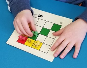The photo shows one hand holding a task card still while the other hand picks up and places a small toy on the task card