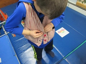 The photo shows a child holds a button hole on one side of a vest with one hand while using the other hand to push a button through the hole