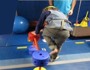 The photo shows a child lifting one leg up to step over an obstacle while standing still and balancing on the other leg