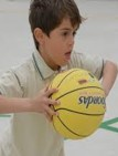 This is a photo of a boy who is holding a basketball with both hands