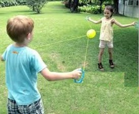 This photo shows children playing zoom ball on a lawn.  They are using their eyes to  follow the ball as it moves along the ropes from one child to another.