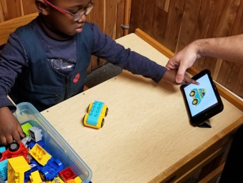 This photo shows a boy who is pointing to an image on the iPad as he selects corresponding Duplo blocks to build a copy of the  car shown on the iPad