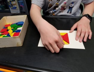 the  photo shows a boy using both hands to arrange parts of a parquetry puzzle.  One hand is holding the task card still while the other hand moves the pieces