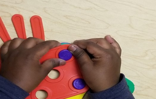 This photo shows how a young  child's hands learn to push a button through a button hole while using the Busy Buttons toy.  One hand is holding the hole still while the other hand is pushing the button through the hole.