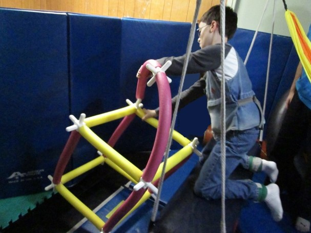 This picture shows a boy who is on a swing and reaching over to add a long pool noodle to a rocket ship he is building