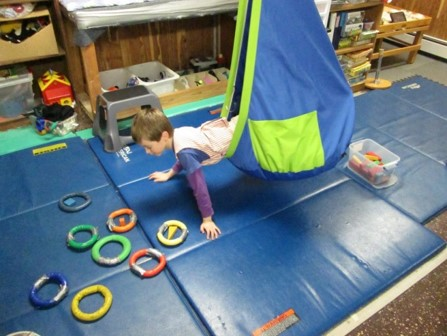 This picture shows a boy who is leaning out of a Fun Zone swing to place a block into rings of matching colors.