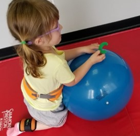 "this is a photo of a child kneeling behind an exercise ball while turning a letter ""C"" into the upright position"