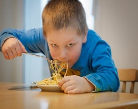 this photo shows a boy who is eating spaghetti with a fork.  He is shoveling the food into his mouth in a very messy way