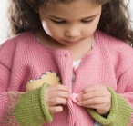 this photo shows a girl who is looking at a button on her sweater.  She is trying to push the button through the hole while using both hands
