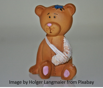 this photo shows a toy stuffed bear who has his arm in a sling