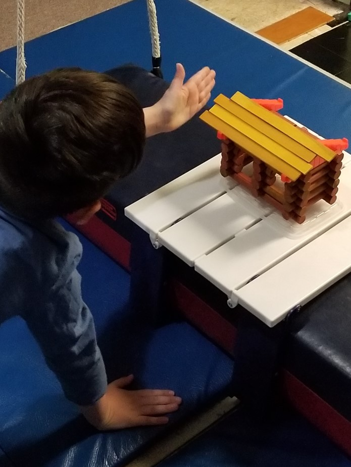 the photo of the boy shows his plan to tap the roof slats gently in order to align them as he completes the top of the Lincoln Log cabin he has built.