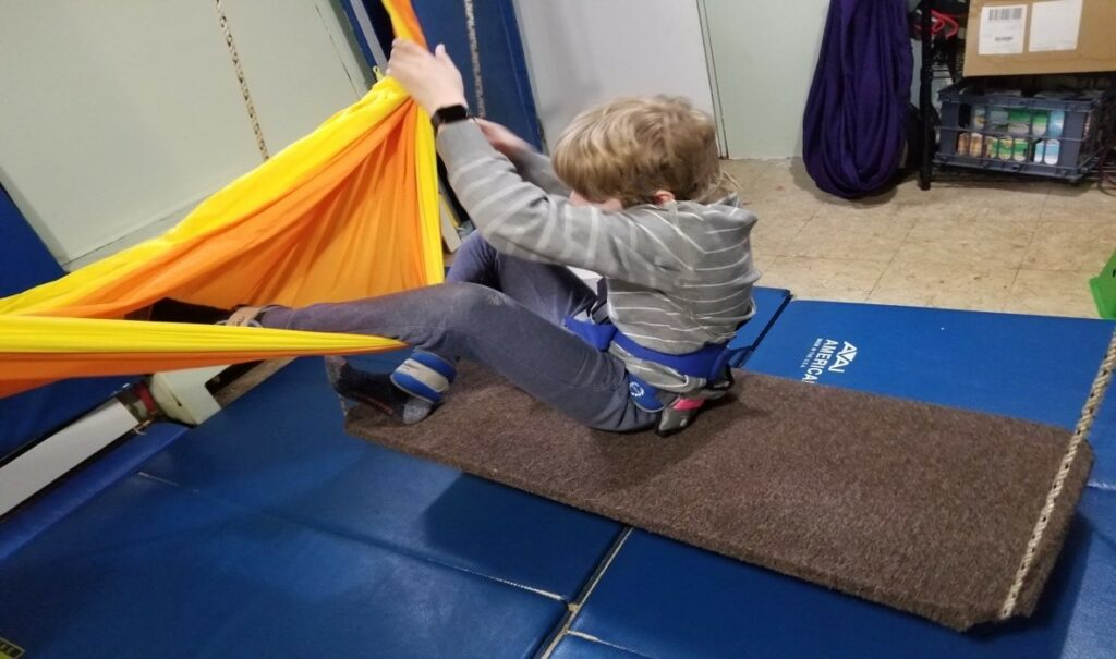 This photo shows a boy who will be moving from one swing into a hammock.  He is  sitting on a platform swing and using both arms to hold the  nearby  hammock open while he moves his legs into the center of the hammock in preparation for transitioning his whole body  into the center of the hammock.