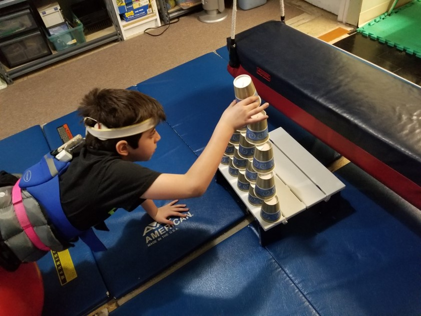 This photo shows a boy performing ball walkouts while stacking a tower of paper cups.  He is using his eyes to carefully guide his hands in placement of each cup