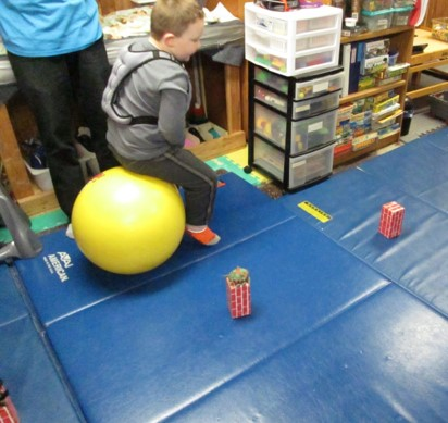 This photo shows a child using a hop ball to hop around obstacles.
