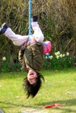 This photo shows a boy hanging upside down and yelling while swinging.