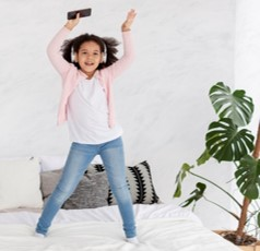 This photo shows a girl jumping on her bed while dancing with headphones.  Her arms are pushed up and out while sings along to add even more input.