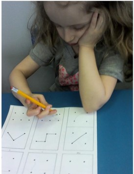 The picture shows a young girl trying to copy a diagram.  She is using one hand to hold her head up, and the other hand to grip the pencil to draw the diagram.  Her pencil grip is very awkward.