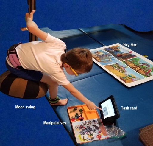 the photo shows a boy sitting on a teardrop shaped swing. He is  keeping  himself steady by holding onto the top of the swing with his left hand, while using his right hand to point to the task card .