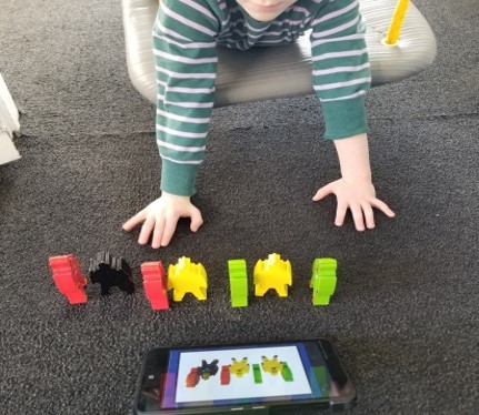 This photo a young boy using a walk out from a doorway swing while he is arranging a lineup of robots as shown on a  digital task card.
