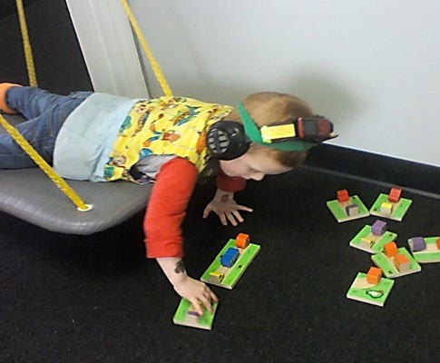 Push ups, resistive exercise from a platform swing is being used to activate attention with this activity. The fun challenge is finding matching wooden car and truck pieces and positioning them as needed to build a roadway.