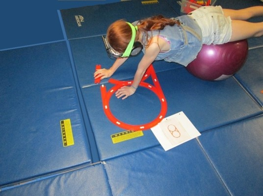 For example,  this older girl is putting  a train track together from a photo of a  layout during her Physioball exercises.  Once again, the resistive exercise stimulates production of brain chemicals that enhance attention.