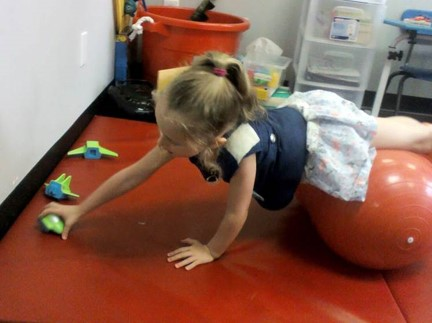 This photo shows a young girl walking out on a physioroll to layout parts of a magnetic vehicle
