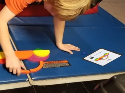 This photo shows a boy walking out on a glider  to arrange parts of a wooden puzzle to match a task card
